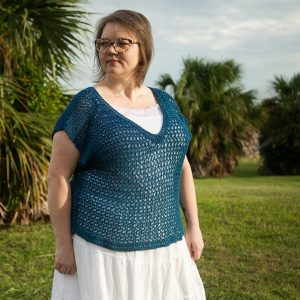 Women wearing blue crochet top with white skirt standing in front of palm tree