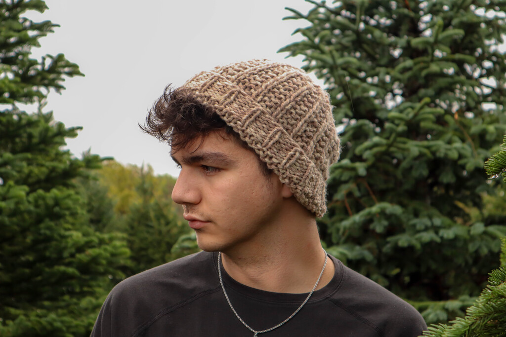 man wearing knit beanie standing in front of forest