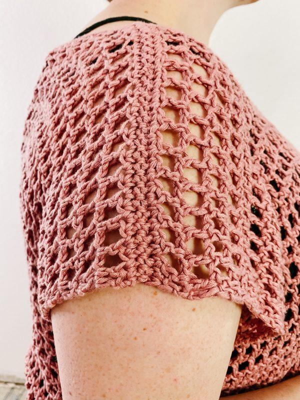 Lady showing shoulder seam of holdo crochet tee