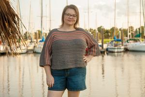 Lady wearing grey sweater with peach stripes, Biel Sweater