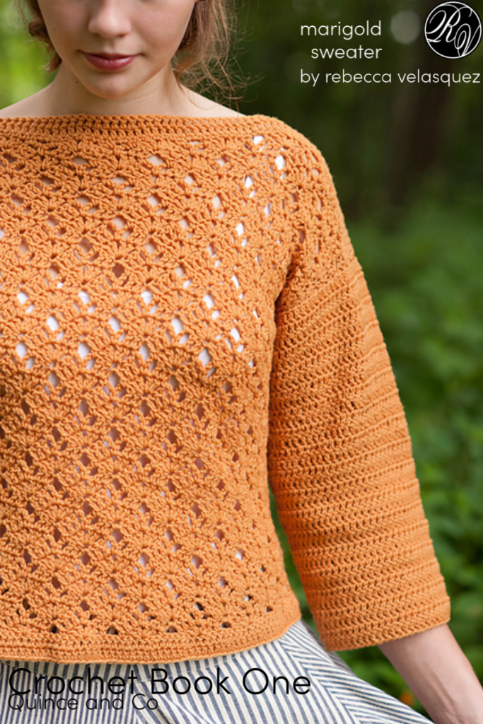 Lady wearing orange crochet sweater standing in front of a forest, marigold sweater