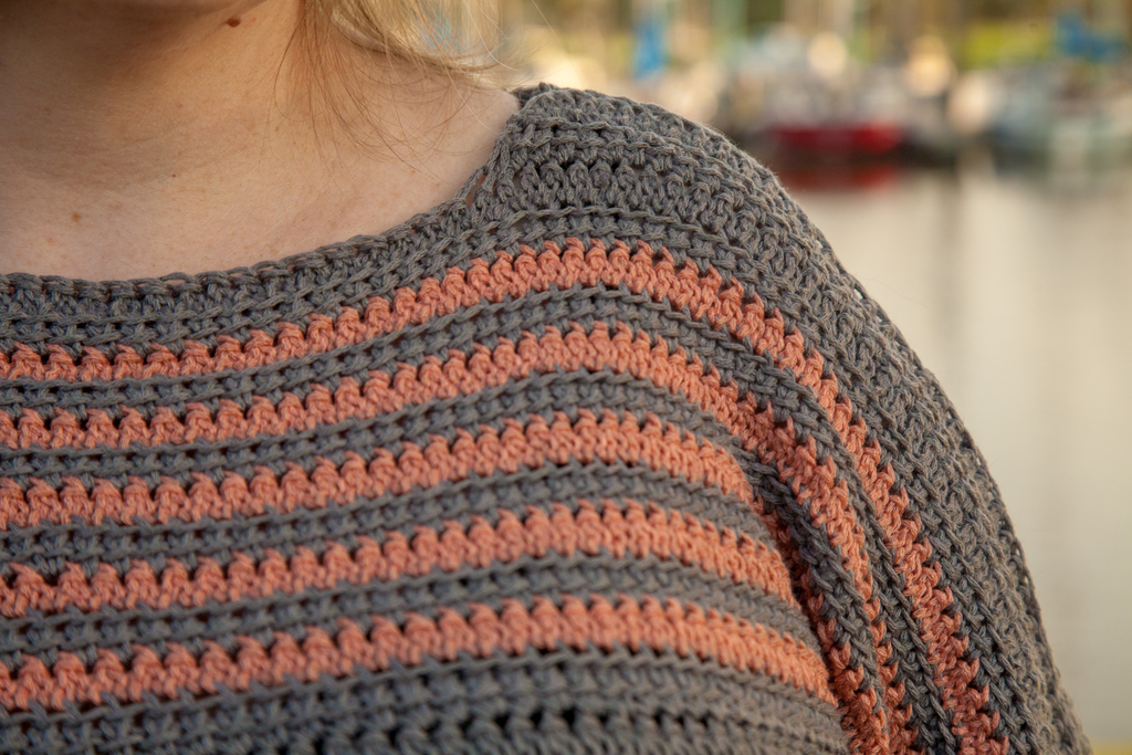 Lady wearing grey sweater with peach stripes, Biel Sweater