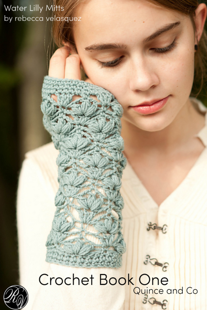 Lady wearing teal colored crochet finger less mitts wearing a white jacket