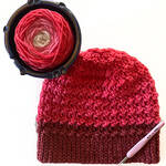 Clancy Orange and Red Crochet Beanie with bernat pop yarn in yarn bowl and tulip hook