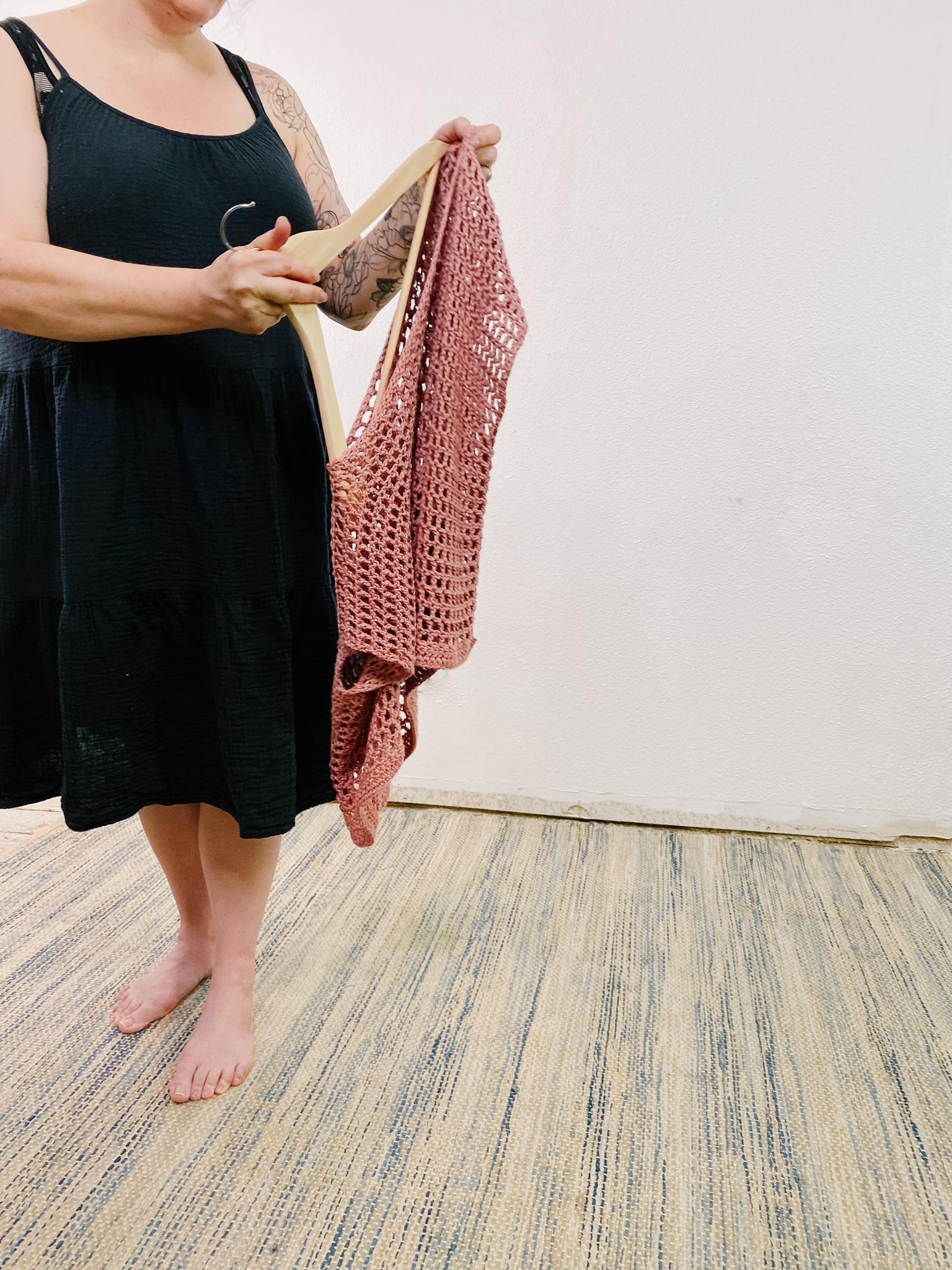 Lady holding pink crochet holdo tee with dark gray dress