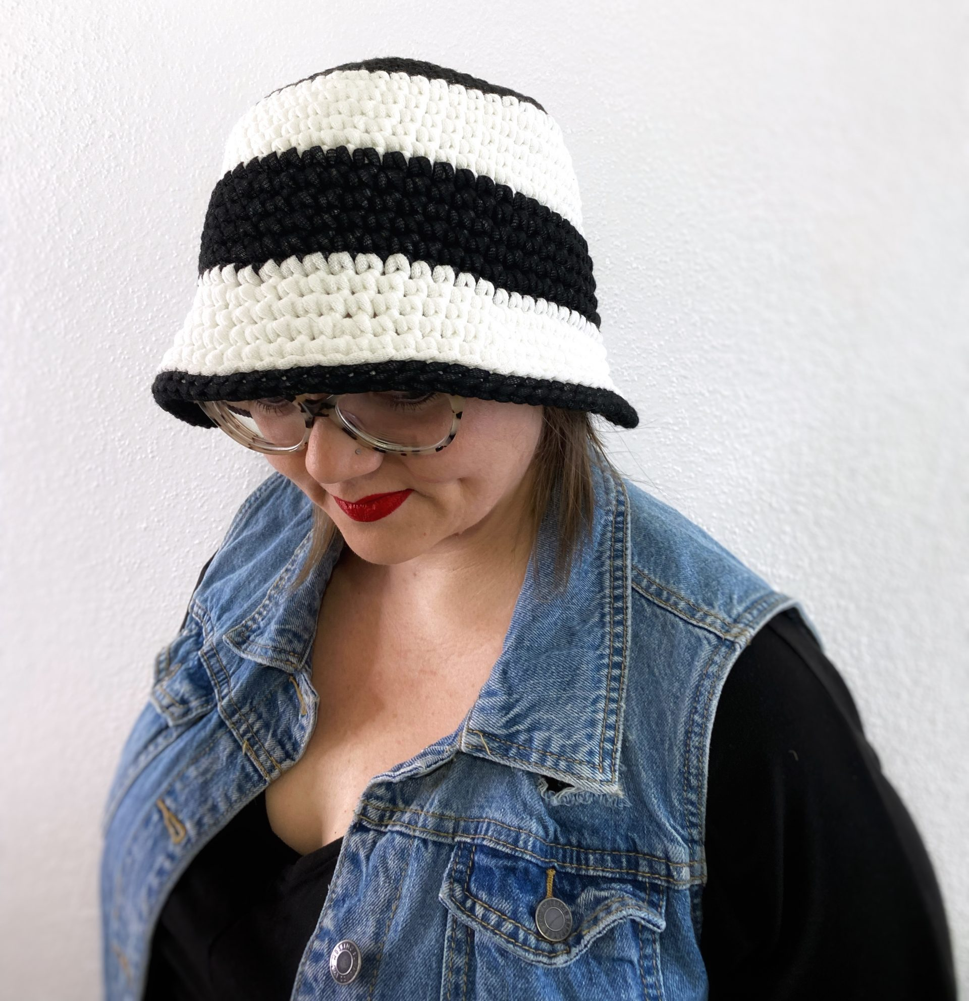 Lady wearing Bickett crochet bucket hat with levi vest and black top